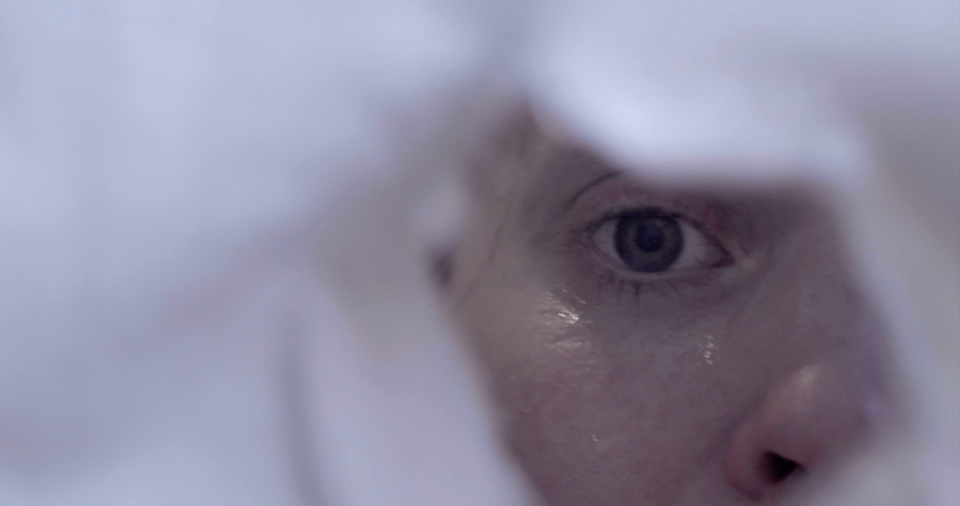 Still from the film A Home Truth showing an eye peeping through a curtain